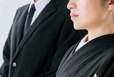 葬儀で喪服を着用している男女のイメージ