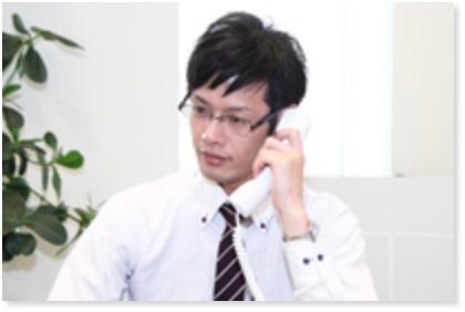 男性の葬儀運営スタッフが電話対応している様子